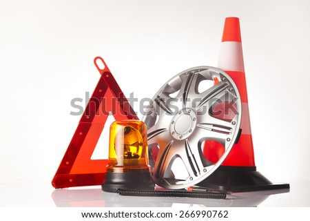 Car accessories - road emergency triangle, commercial vehicle flashing emergency warning lighting with hubcap and traffic cone on white background - stock photo
