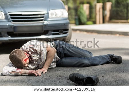Car accident victim lying on street, car in the background.