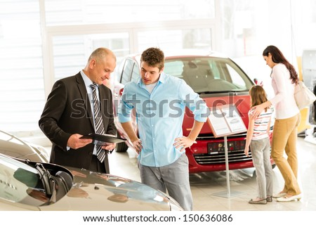 Car agent showing vehicle to young family - stock photo