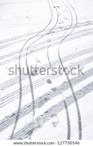 Car and bike tyre tracks and footprints on a snowy road - stock photo