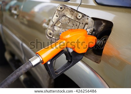 Car and blue Fuel nozzle on a gas station : Selected Focus image : Close up image .