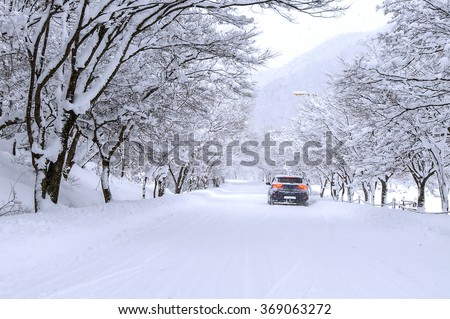 Car and falling snow in winter on forest road with much snow. - stock photo