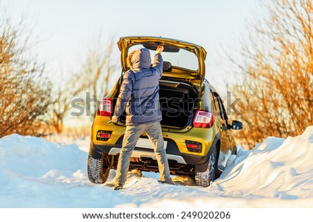 Car and man on snowy road in countryside - stock photo