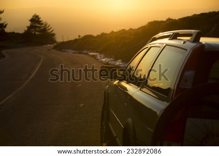 Car at sunset on mountain road - stock photo