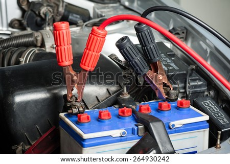 car battery with jumper cable in engine room