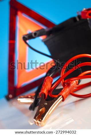Car battery with two jumper cables clipped on vivid moto concept - stock photo
