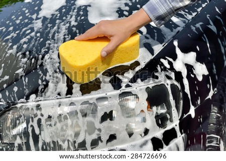 Car Care - Woman washing a car by hand using a sponge - stock photo