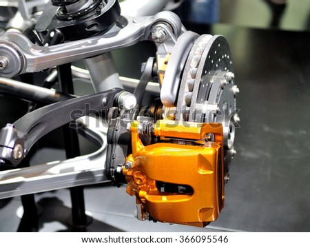 Car ceramic disc brake with yellow caliper, and  front suspension.
