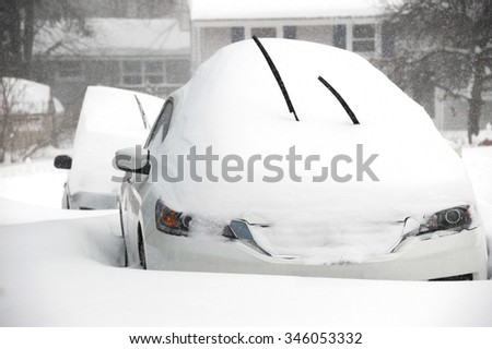 car covered by snow in blizzard