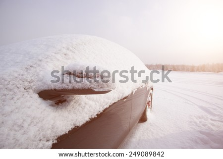 car covered by snow in snow season - stock photo