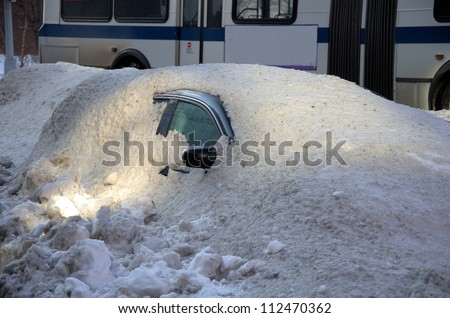 Car covered in snow in the winter blizzard in New York