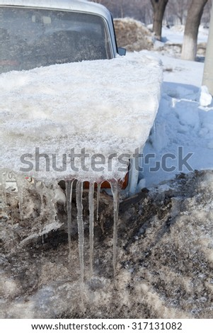 car covered with snow with icicles hanging - stock photo