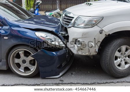 Car crash from car accident on the road in a city between saloon versus pickup wait insurance. - stock photo