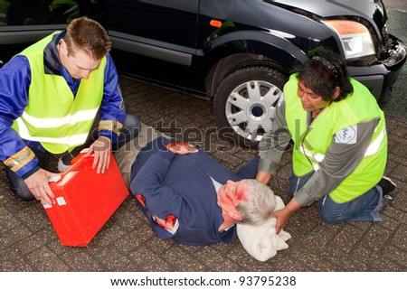 Car crash victim being helped by paramedics (the sleeve badges have been replaced by a non existing logo) - stock photo