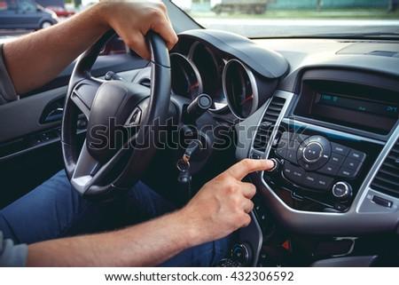 Car dashboard. Radio closeup. Man sets radio - stock photo