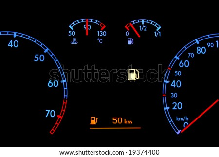 Car dashboard shows low fuel in the night