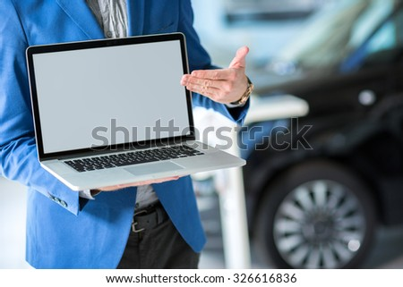 car dealer pointing in the empty screen of the laptop - stock photo