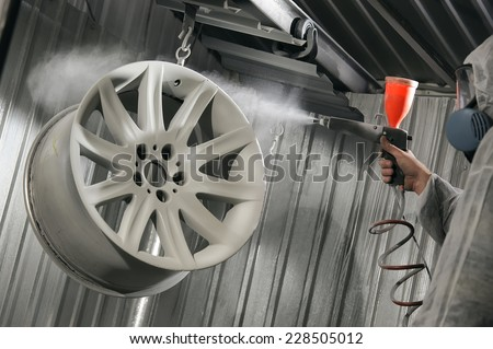 Car diskna restoration painting in service stations. Master paint spraying powder paint - stock photo