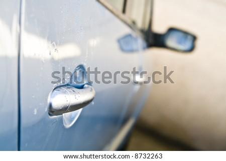 Car door handle in detail with drops of water. - stock photo