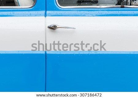 Car door of soft blue and white classic car. - stock photo