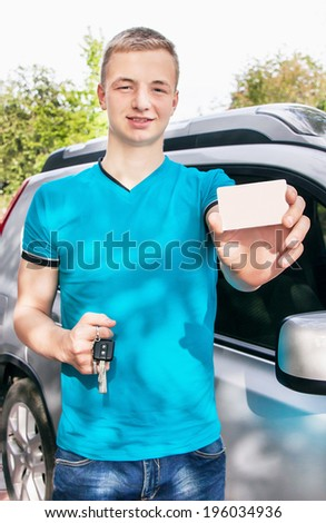 Car driver. Caucasian teen boy showing an empty white card for your message and car key near new car. Happy smiling young man. Travel and rental concept. Close up, outdoor. - stock photo