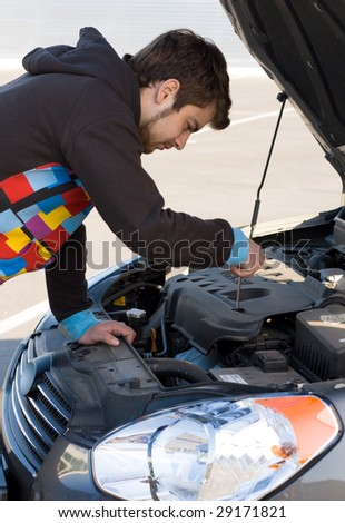 Car driver examining the car's engine on a parking