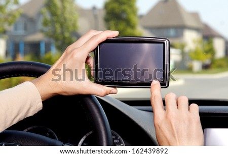 Car driver hands with GPS. Road destination. - stock photo