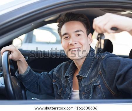 Car driver man smiling showing new car keys - stock photo