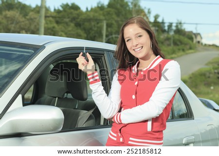 Car driver woman happy showing car keys out window - stock photo