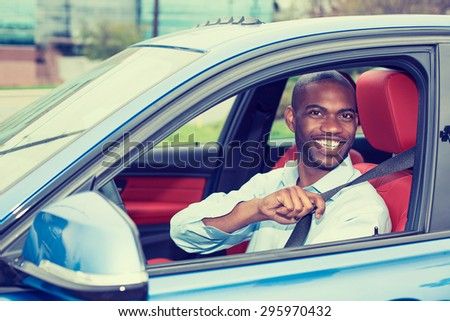 Car driver young man wearing safety belt driving new blue car  in summer. Happy male looking at camera. - stock photo