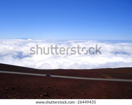 Car driving down from Haleakala National Park.  Highest Peak of Maui, Hawaii - stock photo