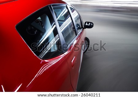 Car driving fast on a parking lot - stock photo