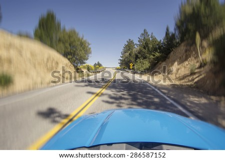 Car driving fast on open mountainous road with bends and turns on a beautiful sunny morning.