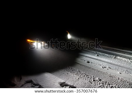Car driving on a snowy road in the middle of the night - stock photo