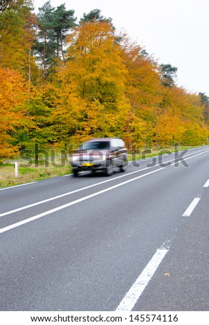 Car driving on country road. Autumn scene, low angle, motion blur. - stock photo