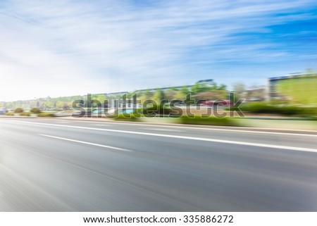 Car driving on road in city background, motion blur - stock photo