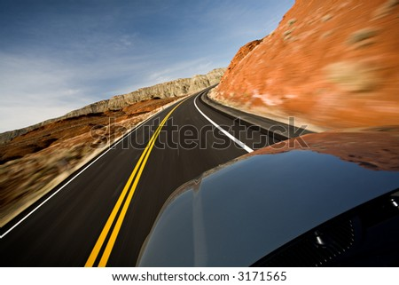 car driving on road through the Bighorn Canyon in Wyoming, motion blur as shot - stock photo