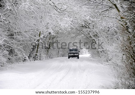 Car driving on winter snow covered country lane through woodland trees - stock photo