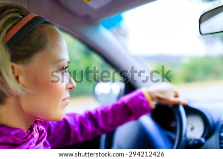 Car driving woman, happy road trip on summer sunny day, young person travel by car looking around at beautiful landscape. Tourism and transportation concept, people traveling on country road. - stock photo