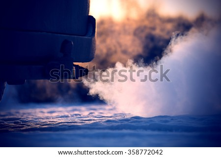Car exhaust pipe, which comes out strongly of smoke in Finland. Focal point is the center of the photo. Background out of focus.  Image includes a effect. - stock photo