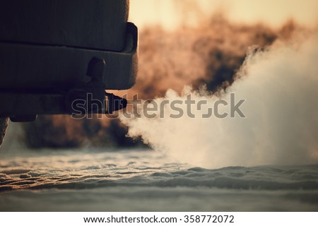 Car exhaust pipe, which comes out strongly of smoke in Finland. Focal point is the exhaust pipe. Background out of focus. Image includes a vintage effect. - stock photo