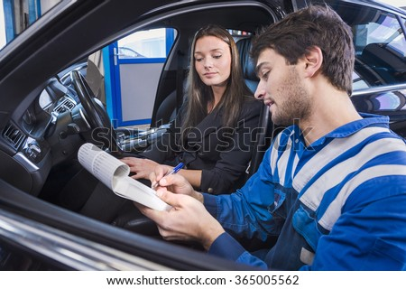 Car expert shows the checklist of repaired items to customer in garage - stock photo