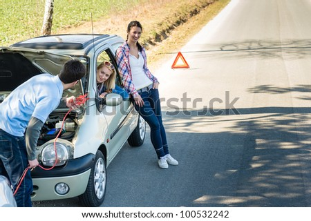Car failure man help two female friends repair engine - stock photo