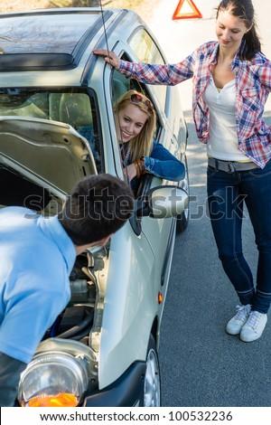 Car failure man help two female friends repair motor - stock photo