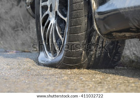 Car flat tire in rainy day - stock photo