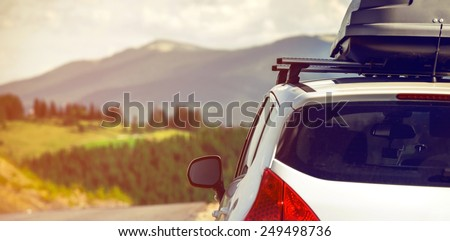 car for traveling with a roof rack on a mountain road - stock photo