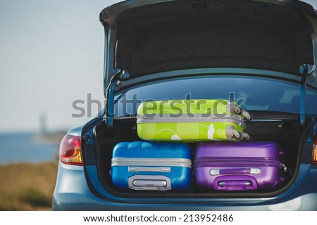 Car full of suitcases and bags to return from summer holidays. overloaded car of a car leaving for the travel - stock photo