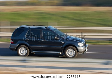 Car going fast on the highway with blurred background - stock photo