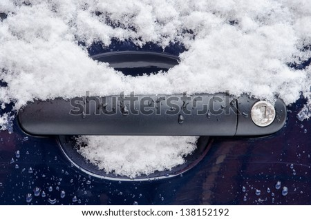 car handle covered with snow during snowing in winter time - stock photo