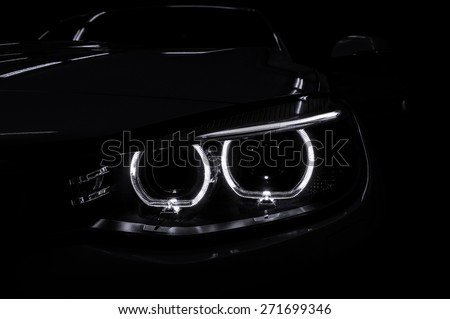 Car headlight with backlight on black background. Exterior detail. - stock photo